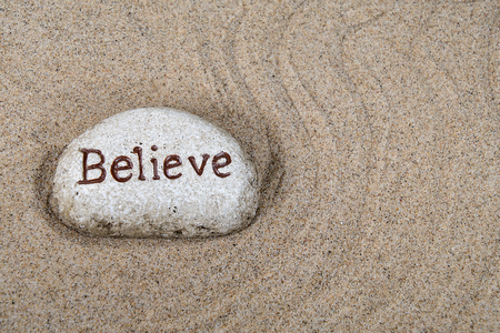 close up of stone with believe text in raked beach sand pattern Stock Photo