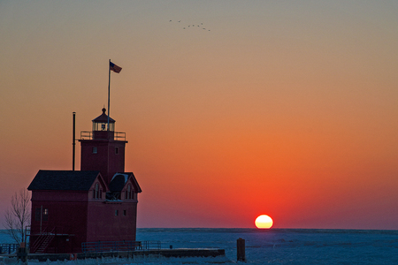 Michigan red lighthouse on Lake Michigan pier in winter at sunset time 스톡 콘텐츠
