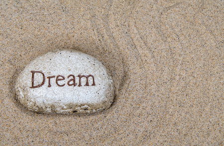 close up of stone with dream sign in raked beach sand pattern