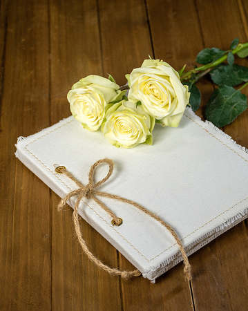 white roses on journal with string bow on rustic wood