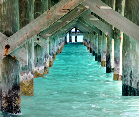 underside view of rustic a wooden pier with turquoise water color in the Bahamas