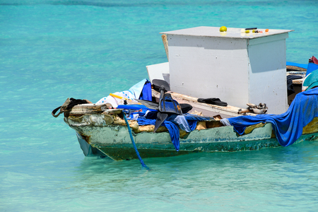 weatherboard old boat cluttered with junk in turquoise ocean water in Nassau, the Bahamas