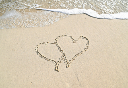 pair of hearts in beach sand with frothy ocean surf Stock Photo