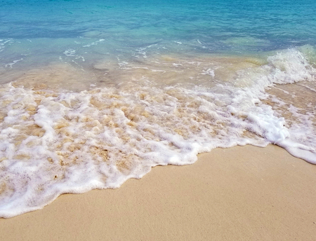 sandy beach and frothy foam surf on turquoise Pacific ocean seashore in Nassau Bahamas