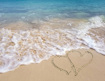 pair of hearts in beach sand with frothy ocean surf and turquoise ocean water Stock Photo
