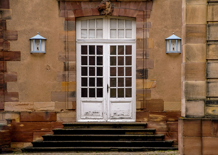 front entrance of old European stone building with closed white double doors and windowpane