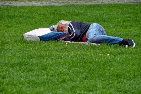 homeless man with bag sleeping on grass