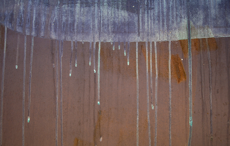 close up of blue dripping blue paint on rusty metal background
