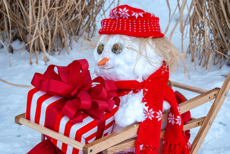 snowman in wooden sled with red bow on Christmas gift Stock Photo