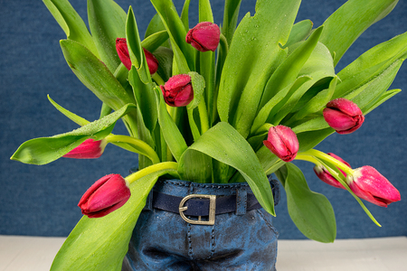 close up of red tulip bouquet in blue jean flower pot on wood