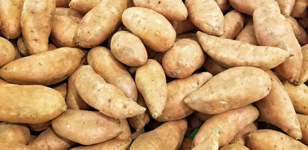 pile of whole sweet potatoes at the food market Stock Photo