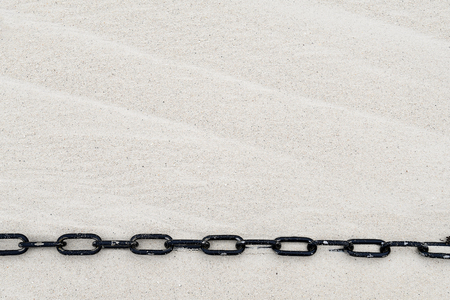 stretched black chain on windswept beach sand Stock Photo