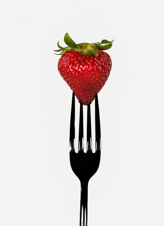 close up of ripe strawberry on black fork isolated on white background Stock Photo