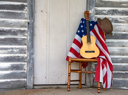 brown hat and six string guitar on wooden chair with American flag by weathered wooden door