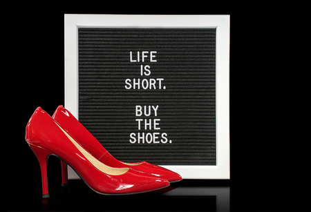 red high heel shoes with quote on white framed message board
