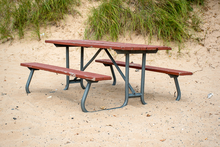 empty picnic table in beach sand with dune grass
