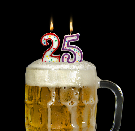 birthday candles for 25th birthday in mug with overflowing beer isolated on black