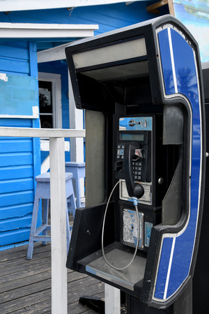 public pay telephone outside blue building in the Bahamas
