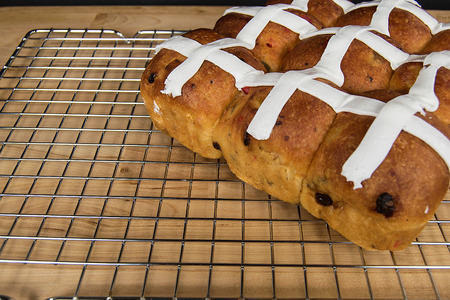 close up of hot cross buns with white icing on metal cooling rack