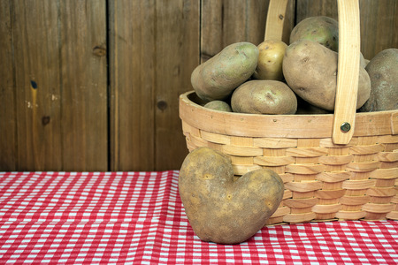 heart shape potato with wooden basket on red and white checked fabric