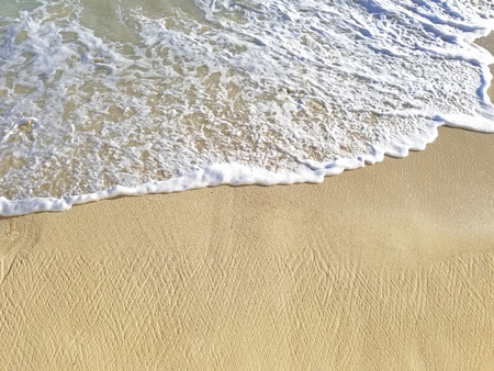 foamy ocean water on tropical beach sand with textured pattern Stock Photo