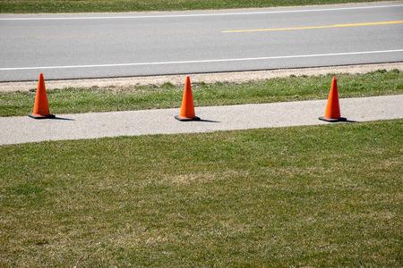 row of orange fluorescent traffic cones on sidewalk