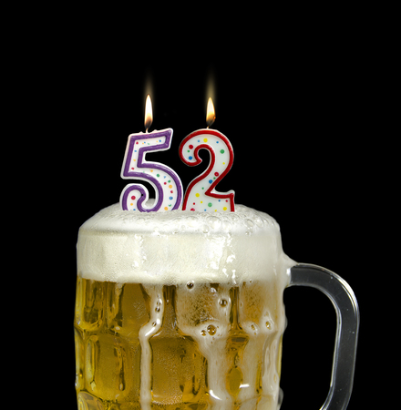 beer overflowing in glass mug with lit candles for 52nd birthday