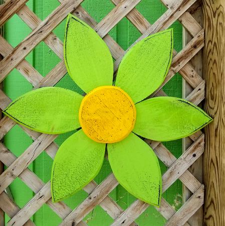 bright green wooden daisy decoration on garden trellis