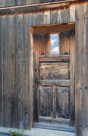 weathered old wooden door with sky reflection in window