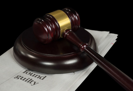 wooden courtroom gavel on newspaper with crime headline
