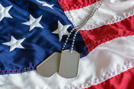 military dog tags on American flag with embroidered stars Stock Photo