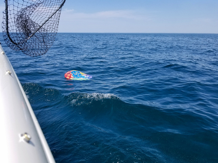deflated helium birthday balloon floating on blue Lake Michigan water Stock Photo