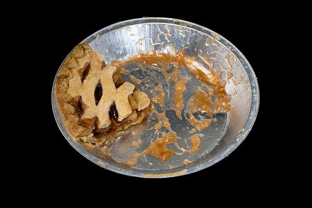 last piece of apple pie in aluminum pan isolated on black