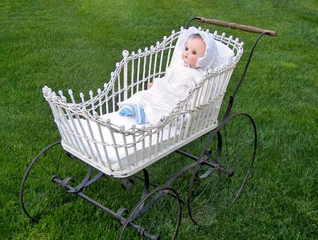 antique baby doll in vintage stroller on grass