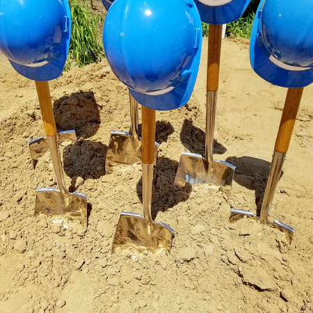 industrial blue hard hats on shovels in dirt for ground breaking ceremony Stockfoto