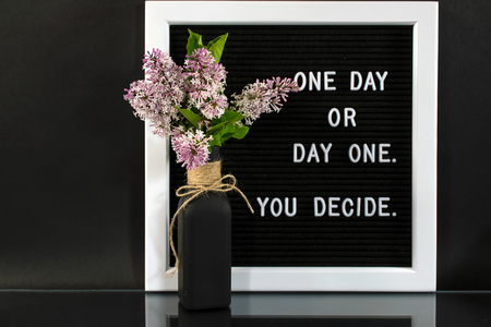 lilac bouquet in black bottle with motivational quote on message board Stock Photo