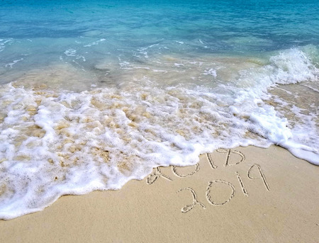 New Year 2019 sign in tropical beach sand with turquoise ocean Stock Photo