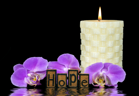 word hope in wood letterpress typeset with pink orchid blossoms and white candle with water reflection effect on black