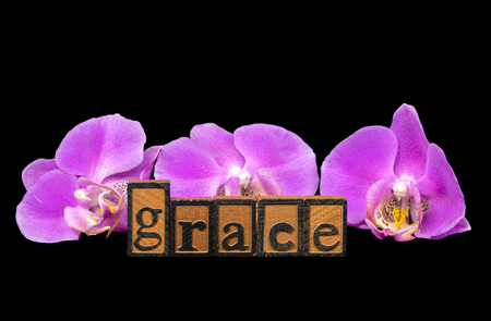 word grace in wooden letterpress typeset with pink orchids on black Stock Photo