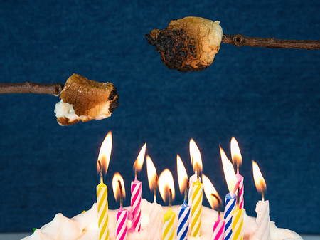 roasting marshmallow on a stick over many birthday candles on a cake