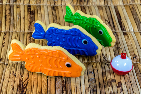 fish cookies with red and white fishing bobber on bamboo mat Stock Photo