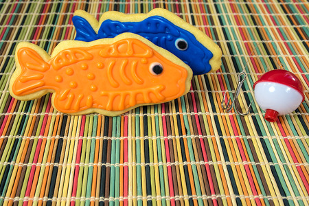 blue and orange icing on fish cookies with fishhook on fishing bobber on striped bamboo mat