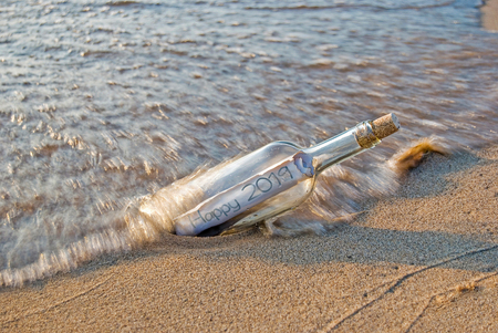 New Year 2019 message in a bottle in wave on beach sand