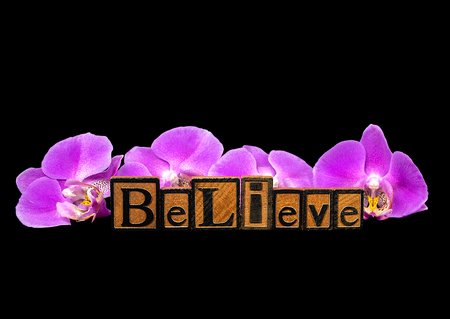 word believe in vintage wooden letterpress typeset with pink orchids on black