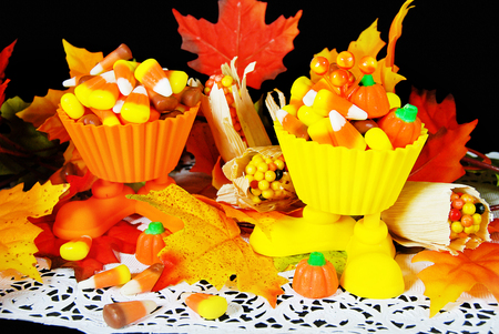autumn candy corn in cups with colorful leaves on white lace doily Stock Photo