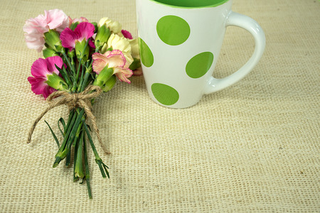 carnation bouquet tied with string and polka dot mug on burlap
