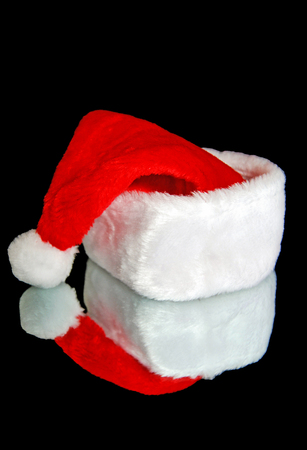 Red and white Santa hat on black mirror with reflection Stock Photo