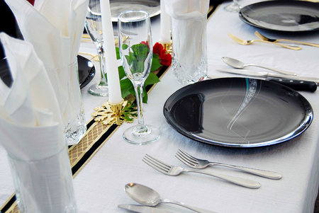 fancy dinner place setting with black plate on white tablecloth