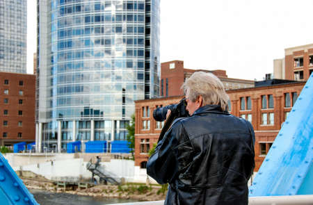 man taking photos with camera on blue bridge in Grand Rapids Michigan with city background Stock Photo