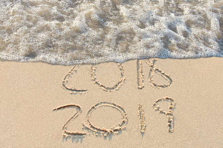 New year 2019 sign in beach sand with frothy surf